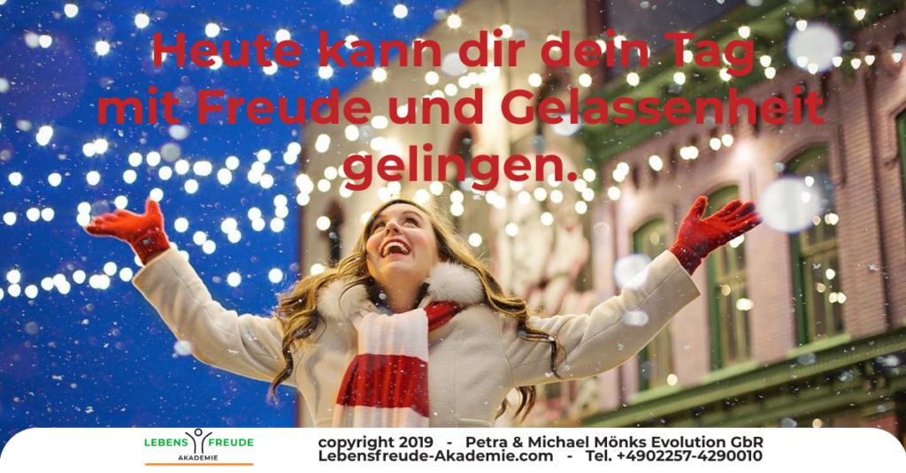 Heute kann dir dein Tag mit Freude und Gelassenheit gelingen. Frau schaut lachend mit ausgebreiteten Armen nach oben - währen Schneeflocken herunterfallen.n